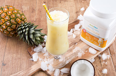 Summer protein drink Pina Colada in a glass with ice cubes